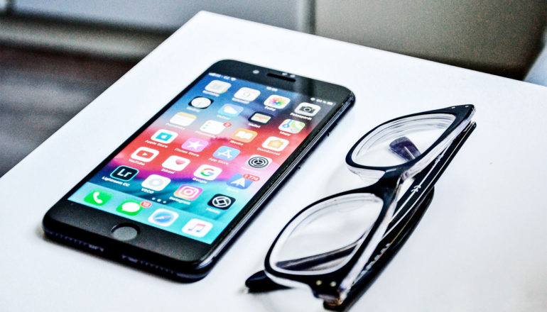 A phone sits on a white table next to a pair of black glasses