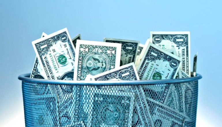 A bunch of 1 dollar bills sit in a trash can, with blue in the background