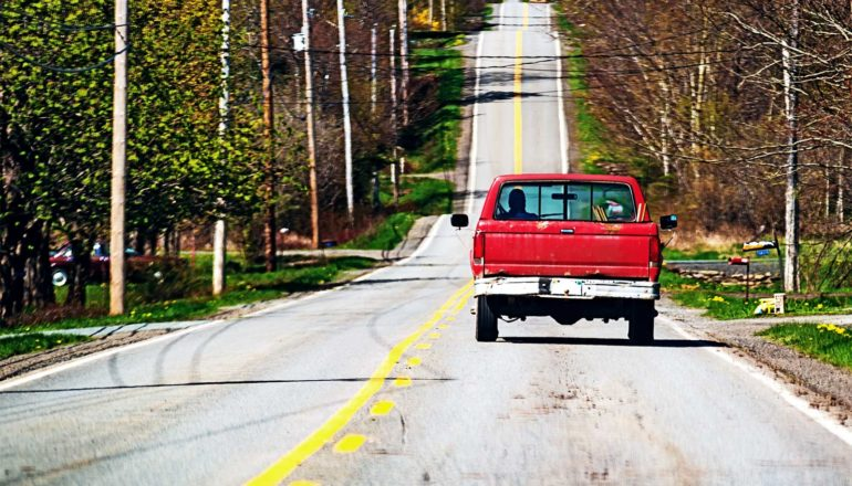 A red truck drives down a rural road, with a few houses on either side