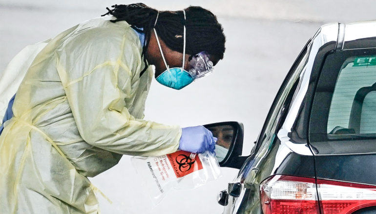A health worker leans over a car window in full protective gear while testing for COVID-19