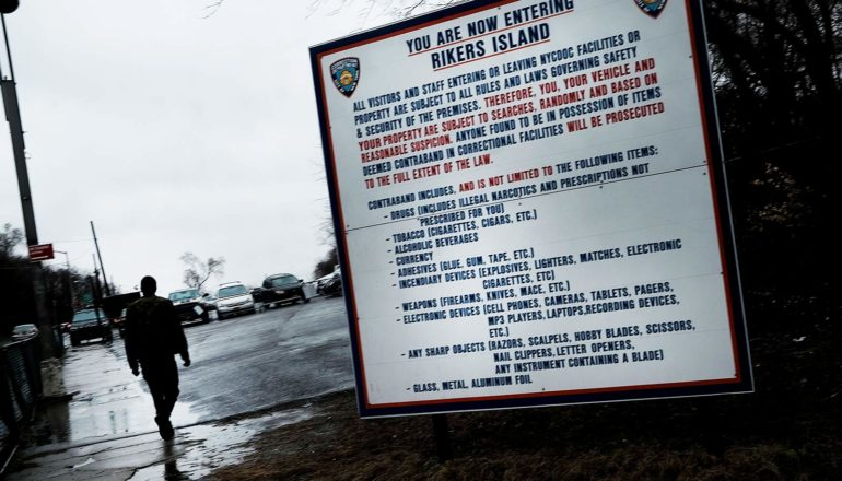"""sign says """"you're now entering Rikers Island"""" and lists contraband items. Person in silhouette walks by"""