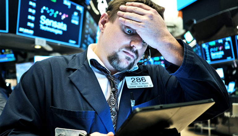 A stock trader puts his hand to his forehead in worry