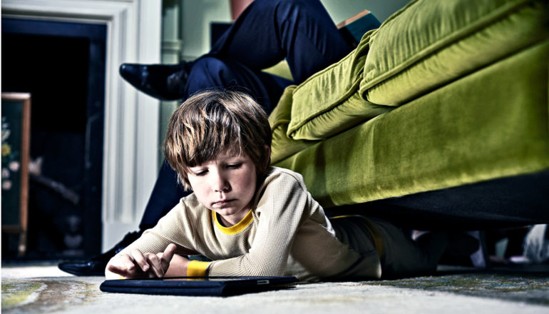 A young boy plays with a tablet computer while laying on the carpet, his legs under a green couch where his father is sitting