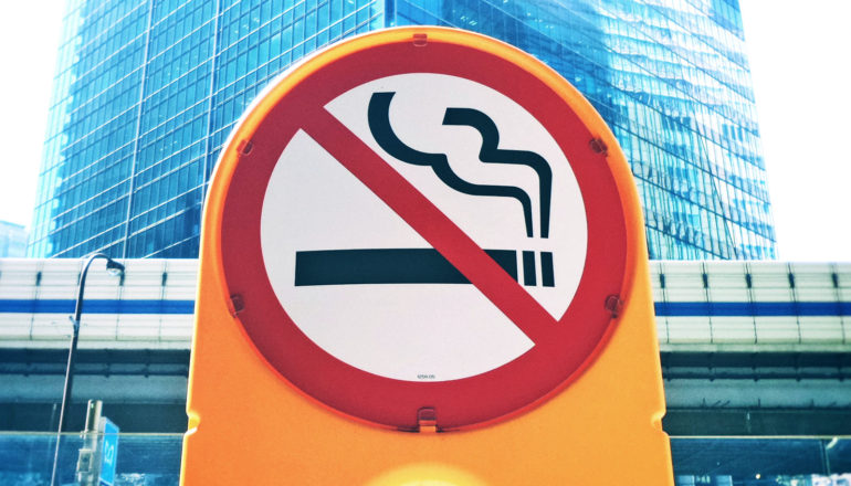 A yellow no-smoking sign stands on a street in front of a large skyscraper in the background
