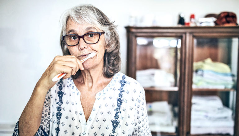 An older woman brushes her teeth