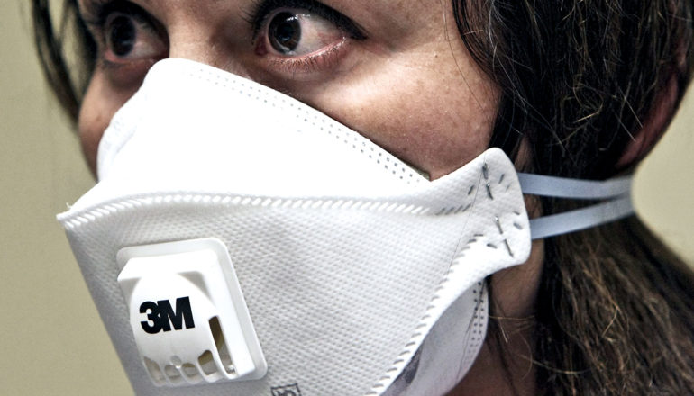 A woman wears an white n95 face mask with the 3M logo on it