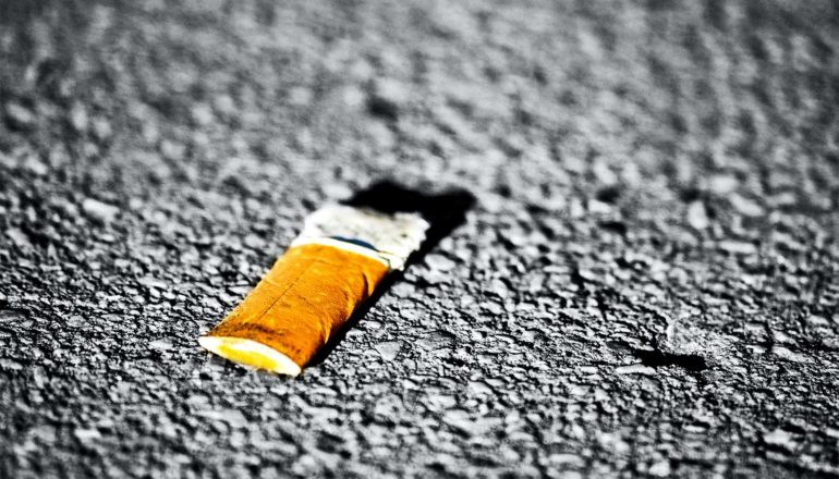 A cigarette butt sits crushed on asphalt