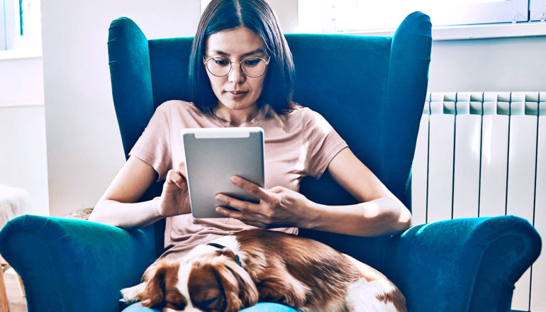 A woman sits in a blue chair and reads a tablet computer, while her dog sits on her lap