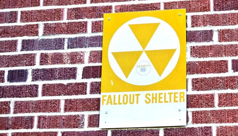 A fallout shelter sign is bolted to a brick wall