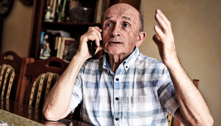 older person on phone looks exasperated with hand in the air
