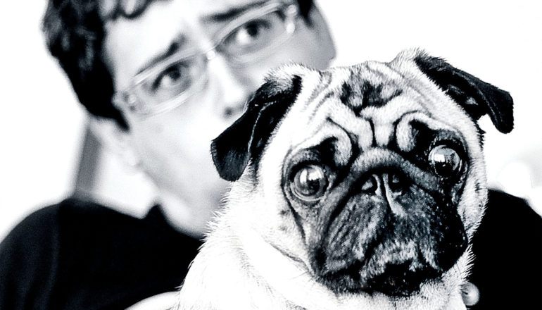 A man sits behind his dog looking worried, with his pug making a similar expression