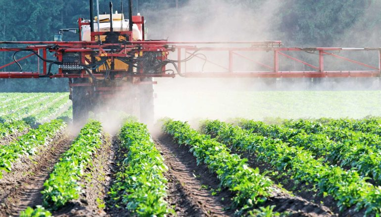 A tractor sprays a field with weed killer