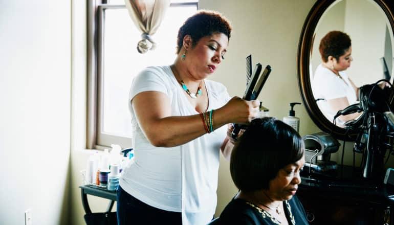 black woman styles customer's hair