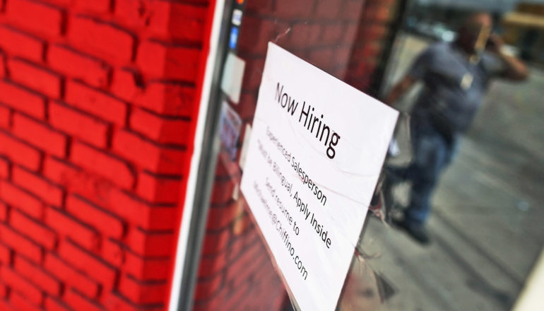 """now hiring"" sign on window"