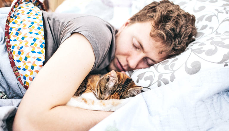 A woman sleeps in bed with her cat close by under the covers