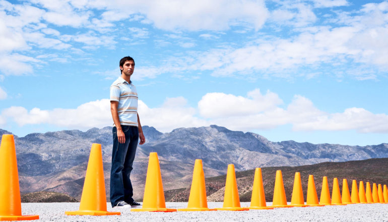 one person stands behind road cones in front of mountain vista