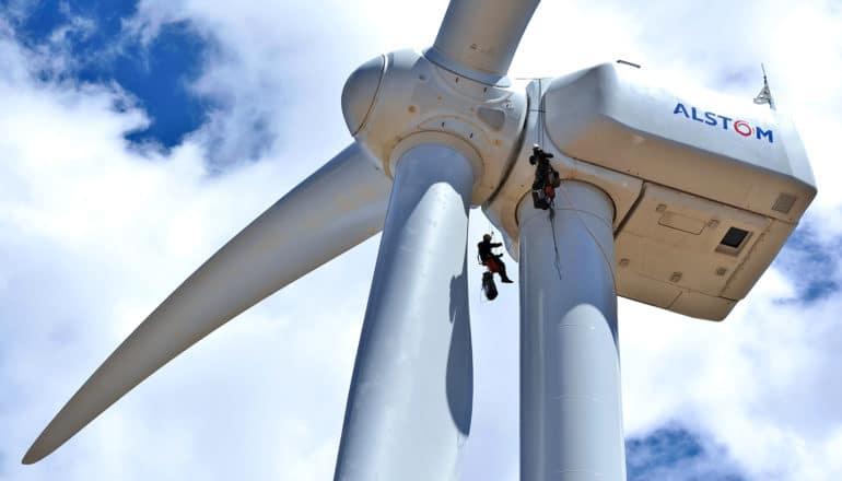 two people climb on wind turbine