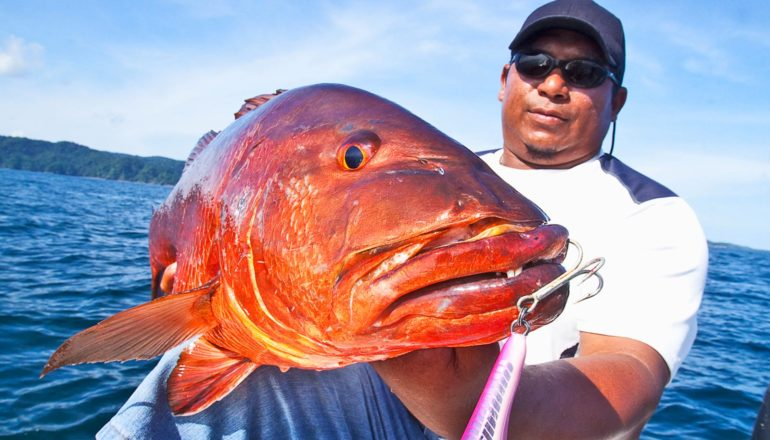 person holds big red fish with hook dangling from its lip