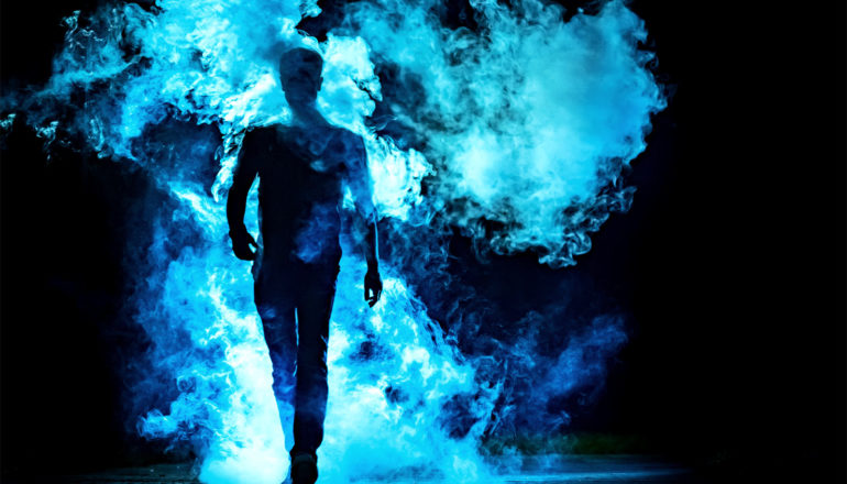 A man in silhouette walks through a cloud of blue smoke against a dark background