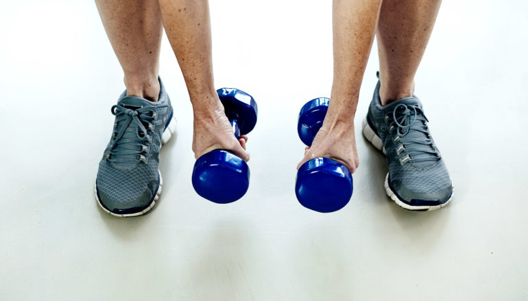A person picks up blue weights, with just their arms and legs visible against a white background