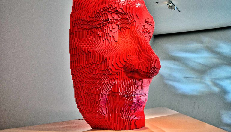 A face made of red lego bricks sits on a wooden pedestal at an art gallery