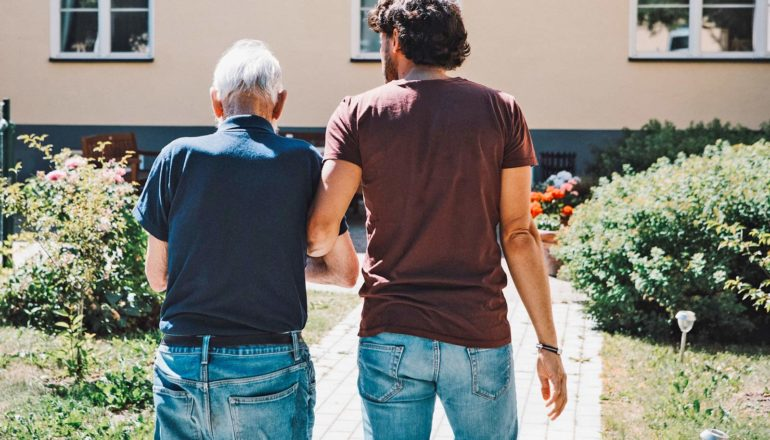rear view of elderly and younger person walking outdoors with linked arms