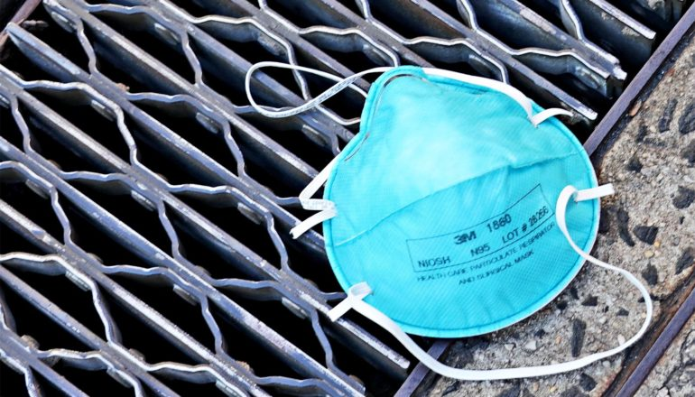 A blue medical mask sits on a sewer or subway grate