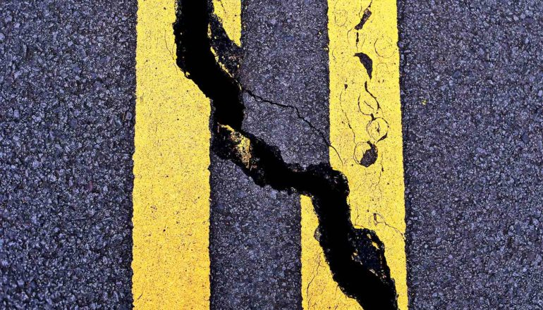 A road with two solid yellow stripes is cracked diagonally down its center