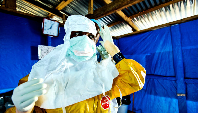 A health worker gets help in putting on protective gear