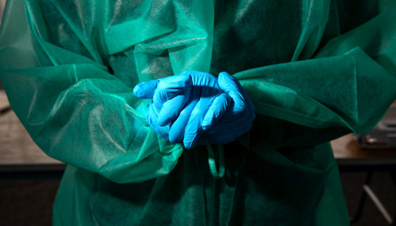 midsection of person in protective gown and medical gloves holding clasping own hands