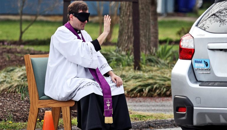 A blindfolded priest in white robes with a purple sash holds his hand up to make the sign of the cross towards a car near him in the parking lot
