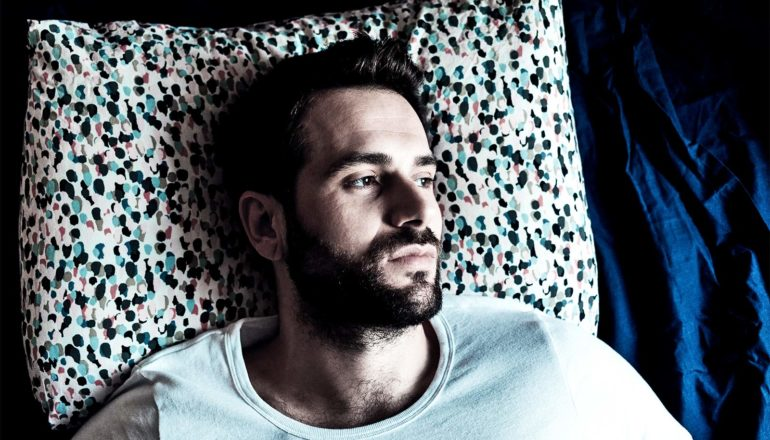 A young bearded man in a white t-shirt lays in bed wide awake