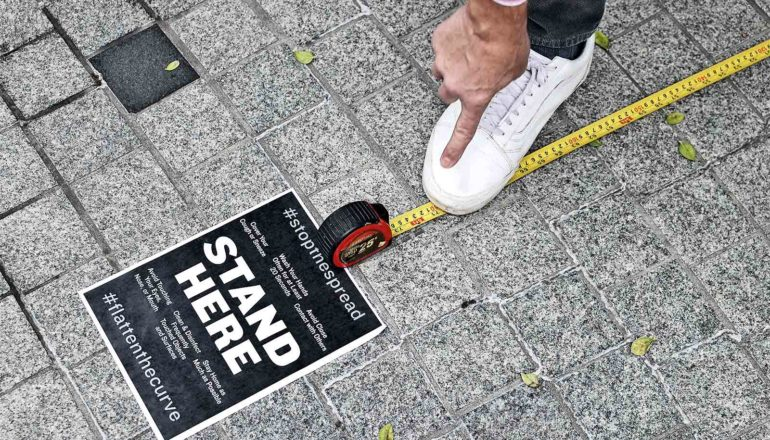 """A person measures 6 feet with a tape measure, steps on the yellow tape with a white shoe, and points at the spot. A black sign reads """"Stand Here."""""""