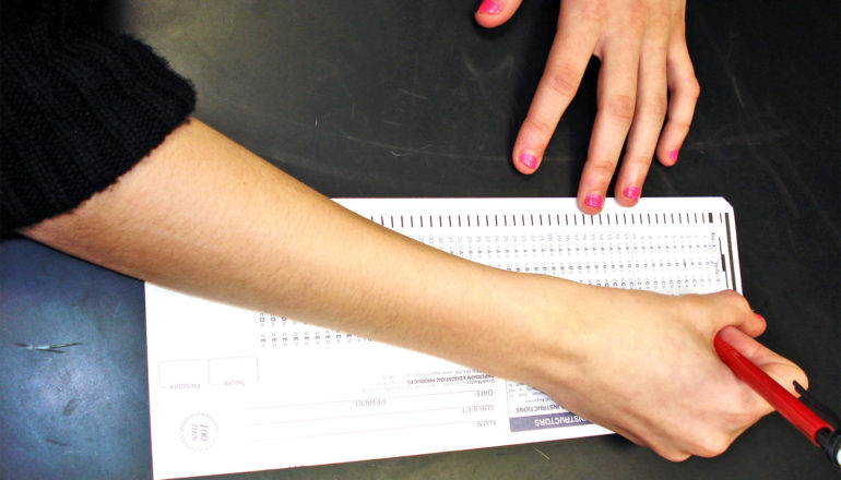 A student fills out a standardized test scantron on a black table