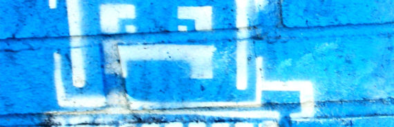 A computer with a frowning face is painted on a bright blue brick wall in white