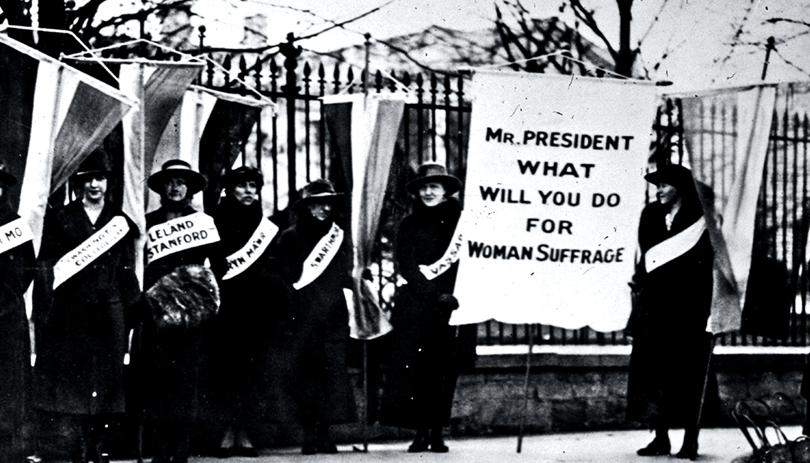 "Women picket outside the White House, one holding a sign that reads, ""Mr. President What Will You Do For Woman Suffrage"""