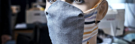 The prototype face mask on a mannequin head. The mask has a gray fabric front section and multi-colored bands of fabric around the back of the head and under the chin