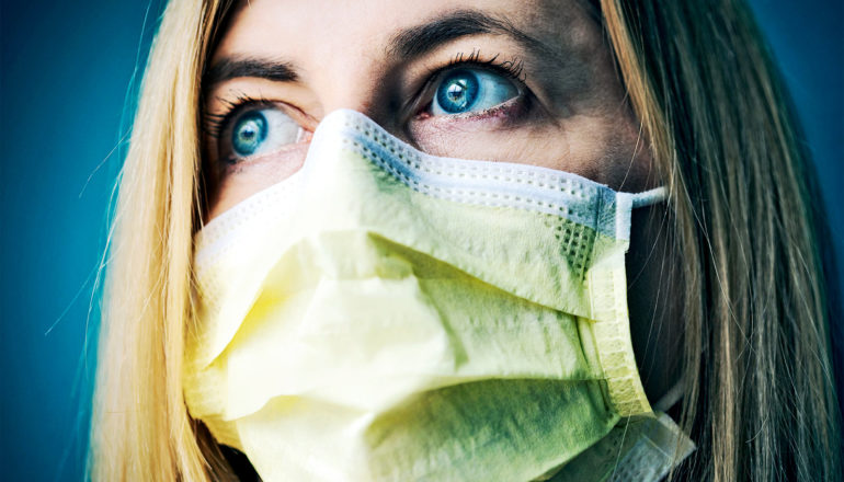 A woman wearing a yellow face mask looks into the distance with worry