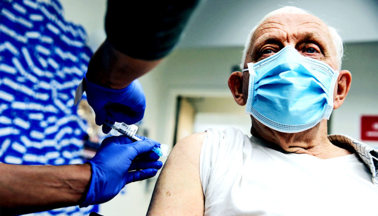 An older man gets a COVID-19 vaccine while wearing a face mask