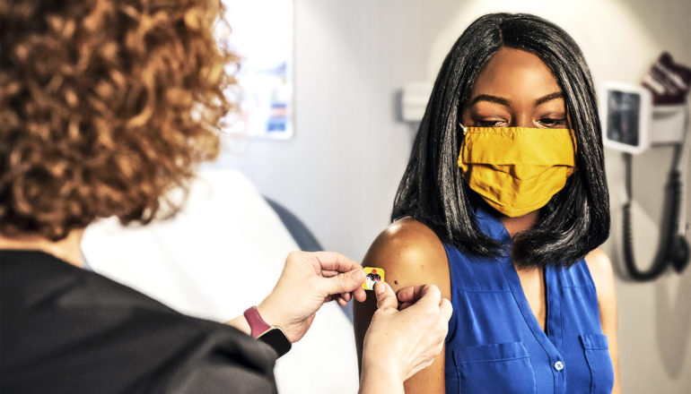 A health worker puts a bandage over a vaccine site on a woman's arm