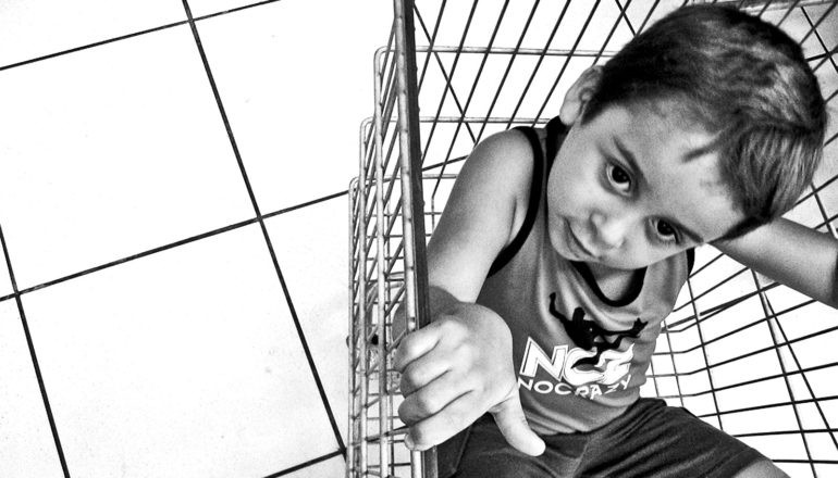 A child in a grocery cart looks up at the cart