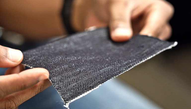 A researcher holds a piece of the black fabric