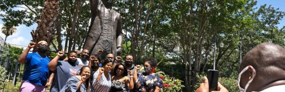 A group poses for a picture in front of a statue of Al Edwards