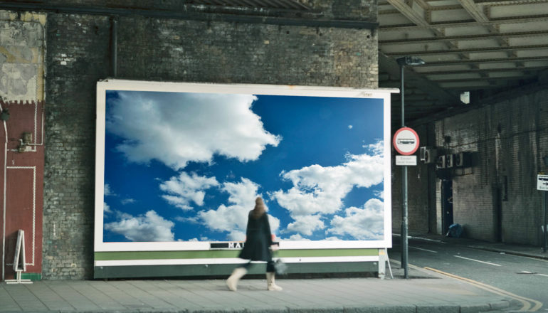 person in grimy underpass walk past billboard image of blue sky with white clouds