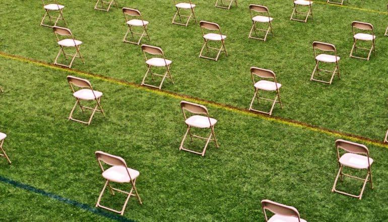 Chairs sit six feet apart on a green field