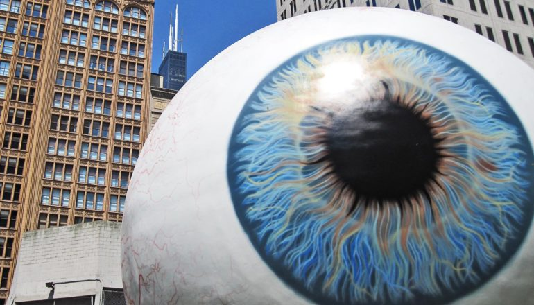 A giant statue of an eyeball sits in front of skyscrapers and a blue sky