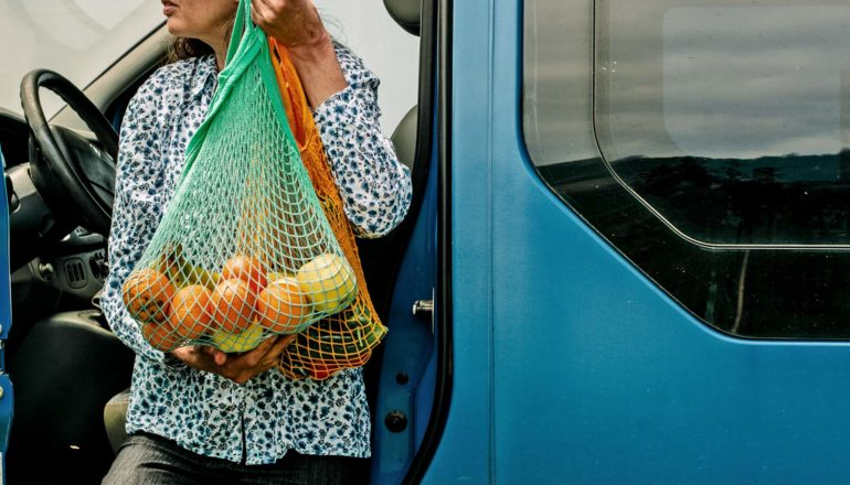 person holds bag of citrus as they leave blue van