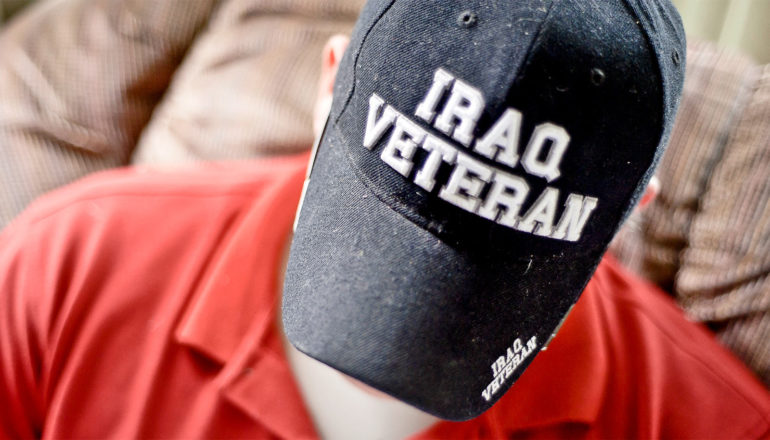 """A man looks down while wearing a baseball cap that reads """"Iraq Veteran"""" and sitting on a couch"""